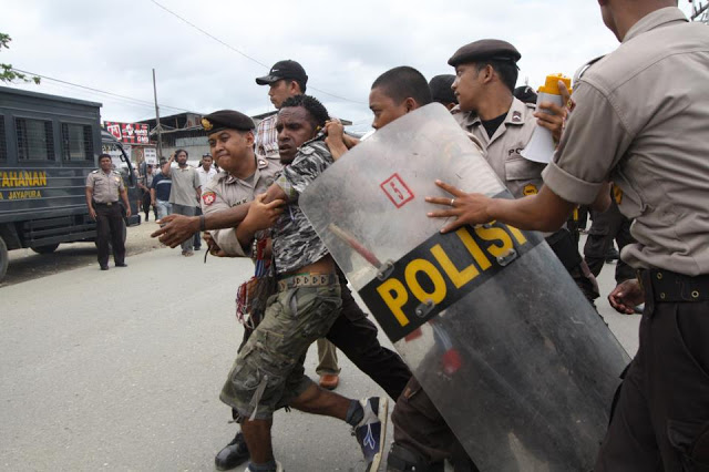 West Papuan activist being arrested by Indonesian riot police