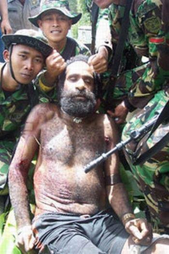 "Indonesian soldiers pose grinning with their ""trophy photo"" corpse of Yustinus Murib, a West Papuan leader they have killed. 2003."